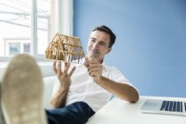 Uomo d'affari fiducioso guardando casa modello in ufficio — Foto stock