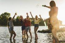 Grupo de amigos felizes em um rio ao pôr-do-sol — Fotografia de Stock