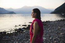 Bella giovane donna sul lungolago guardando la distanza — Foto stock
