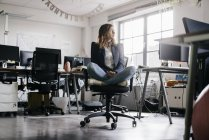 Businesswoman sitting cross-legged on office chair — Stock Photo