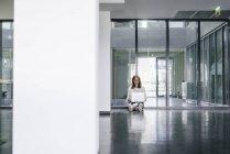 Geschäftsfrau sitzt in leerem Büro auf dem Boden und benutzt Laptop — Stockfoto