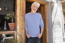 Пожилой мужчина в полосатой толстовке стоит перед рестораном и смотрит в камеру — стоковое фото