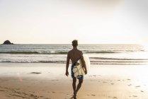 Молодой человек, идущий по пляжу с доской для серфинга — стоковое фото