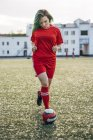 Young woman playing football on football ground running with ball — Stock Photo
