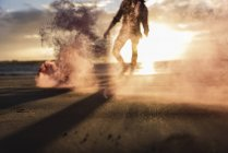 Young man running on beach at sunset with colorful smoke — Stock Photo