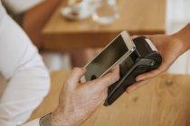 Pago sin contacto con teléfono inteligente en la cafetería - foto de stock