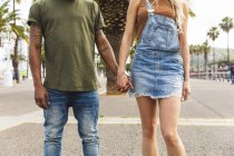 Spain, Barcelona, multicultural young couple holding hands on promenade, partial view — Stock Photo