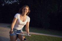Jeune femme caucasien conduisant le vélo en stationnement — Photo de stock