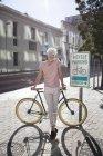 Портрет посміхаючись зрілої людини в місті спираючись на велосипеді — стокове фото