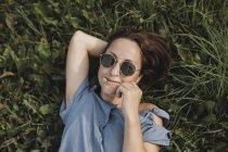 Портрет улыбающейся женщины в солнечных очках, лежащей в траве с цветами во рту — стоковое фото