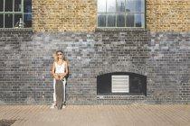 Mujer joven de pie con monopatín en la pared de ladrillo en la ciudad - foto de stock