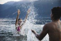 Jeunes couples heureux jouant dans un lac — Photo de stock