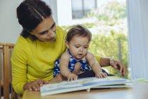 Madre e figlia bambino guardando i bambini libro — Foto stock