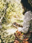 Woman leaning against olive tree using cell phone — Stock Photo