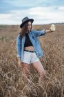 Young woman wearing hat and denim jacket taking selfie with camera in a corn field — Stock Photo