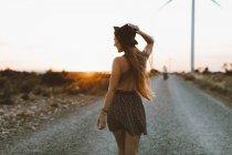 Vista posteriore della giovane donna che cammina sulla strada rurale in serata — Foto stock