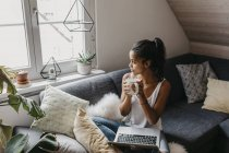 Young woman with laptop and cup of coffee sitting on couch at home looking out of window — Stock Photo