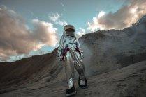 Spaceman exploring nameless planet, walking in dust cloud — Stock Photo