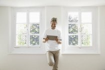 Mature man standing at window and using digital tablet — Stock Photo