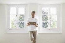Зріла людина, що стоїть у вікні і за допомогою цифрової планшета — стокове фото