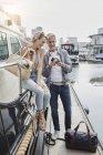 Мужчина и молодая женщина с разницей в возрасте с камерой на пристани рядом с яхтой — стоковое фото