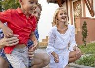Família feliz no jardim de sua casa — Fotografia de Stock