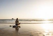 Молодая женщина практикует йогу на пляже, сидит на доске для серфинга, медитирует — стоковое фото