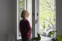 Mature woman at home opening window — Stock Photo
