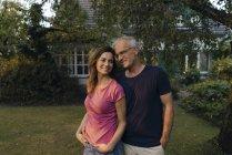 Улыбающаяся зрелая пара, стоящая в саду дома — стоковое фото