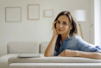 Porträt einer reifen Frau, die zu Hause auf dem Sofa ruht — Stockfoto