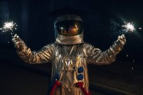 Spaceman standing on road at night and holding sparklers — Stock Photo