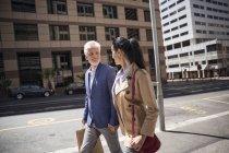 Feliz pareja madura caminando en la ciudad cogido de la mano - foto de stock