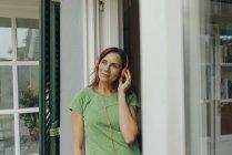 Mulher madura em pé na porta do terraço ouvindo música com fones de ouvido — Fotografia de Stock