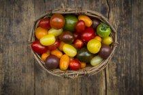 Basket of Heirloom tomatoes on wood — Stock Photo