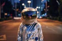 Spaceman standing on street in city at night — Stock Photo