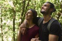 Щасливі пара стоячи в лісі і дивлячись — стокове фото