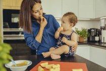 Мать и дочка едят яблоки на кухне вместе. — стоковое фото