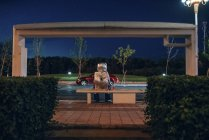 Spaceman sitting on bench at bus stop at night — Stock Photo