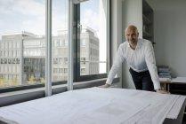Улыбающийся лысый бизнесмен, стоящий в офисе за столом со строительным планом и смотрящий в камеру — стоковое фото