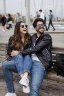 Щаслива молода пара відпочиває на лавці в міській гавані — стокове фото
