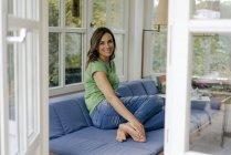 Sonriente mujer madura sentada en el sofá en casa - foto de stock