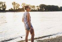 Sorridente giovane donna in piedi a riva del fiume — Foto stock