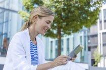 Mujer de negocios rubia sonriente usando tableta - foto de stock