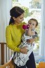 Усміхнена мати набирає свою дитину дівчина з ліжка — стокове фото