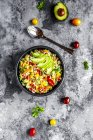 Bowl of bulgur salad with bell pepper, tomatoes, avocado, spring onion and parsley — Foto stock