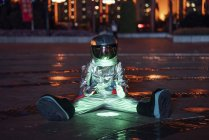 Spaceman sitting at lamp on city square at night and warming hands — Stock Photo