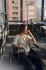 Donna d'affari disabile seduta in sedia a rotelle nella stanza dell'ufficio con finestra — Foto stock
