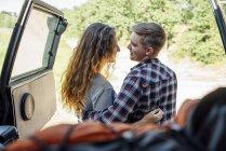 Couples romantiques faisant le voyage de route, embrassant près de la voiture — Photo de stock