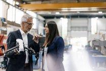 Бизнесмен и предпринимательница на высокотехнологичном предприятии, обсуждают производство беспилотников — стоковое фото