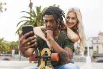 Portrait of multicultural young couple taking selfie with smartphone — Stock Photo